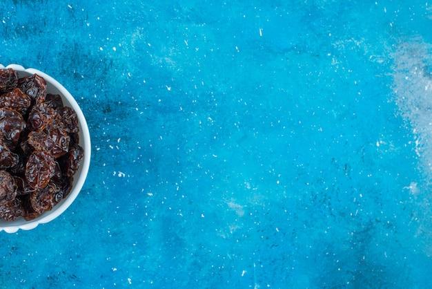 Prugne secche stuzzicanti in una ciotola, sul tavolo blu.