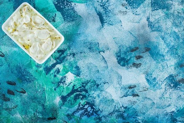 Dushbara dentifricio in un piatto, su sfondo blu.