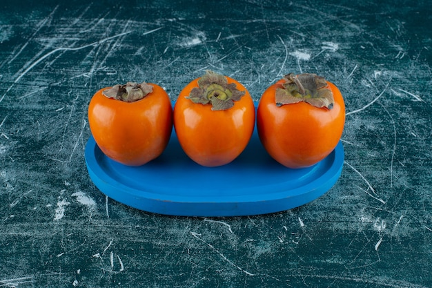 大理石の背景に、木の板に歯ごたえのある柿の果実。高品質の写真