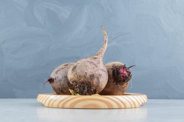 Зубастый редис в деревянной тарелке на мраморном фоне.