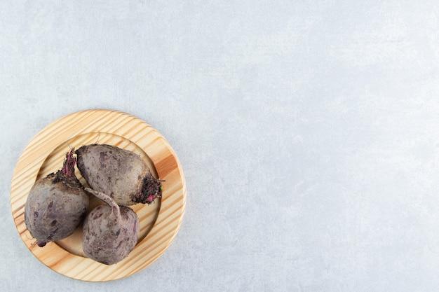 Зубастый редис на деревянной тарелке, на мраморе.