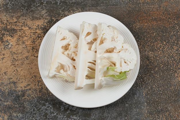 Dentellatura di cavolfiore a fette sul piatto, sulla superficie del marmo