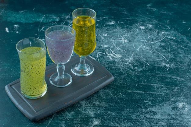 青い背景に、木製トレイのグラスに歯ごたえのある様々なジュース。高品質の写真