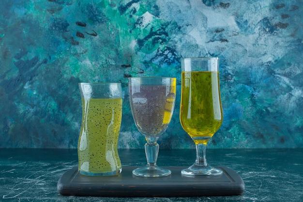 青いテーブルの上に、木製のトレイのグラスに歯ごたえのある様々なジュース。