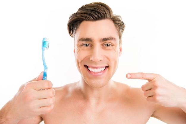 青い歯ブラシを指している歯の幸せな若い男