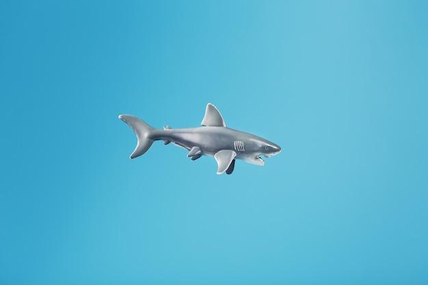 空き容量のある青い背景に歯ごたえのあるサメのおもちゃ。