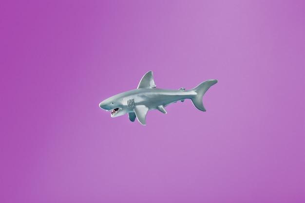 空き容量のあるピンクの背景に歯ごたえのあるサメのおもちゃ。