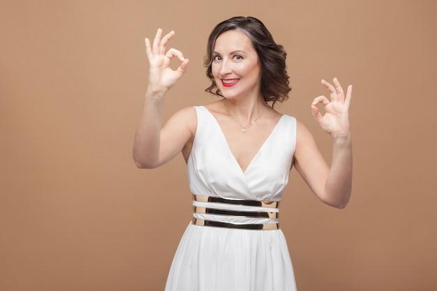 확인 표시를 보여주는 하얀 드레스에 이빨 미소 여자. 흰 드레스, 붉은 입술, 짙은 곱슬머리를 한 감정적인 여성. 스튜디오 촬영, 실내, 베이지색 또는 밝은 갈색 배경에 격리