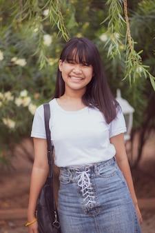 リラックスして幸せなアジアのティーンエイジャーのこぼれるような笑顔