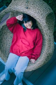 집 테라스에서 대나무 그네에 앉아 아시아 십대의 이빨 웃는 얼굴