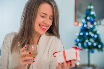 Toothy smiling woman with red lips holding gift box and vine glass. Happy woman holding gift box. Champagne drink. Vine glass.