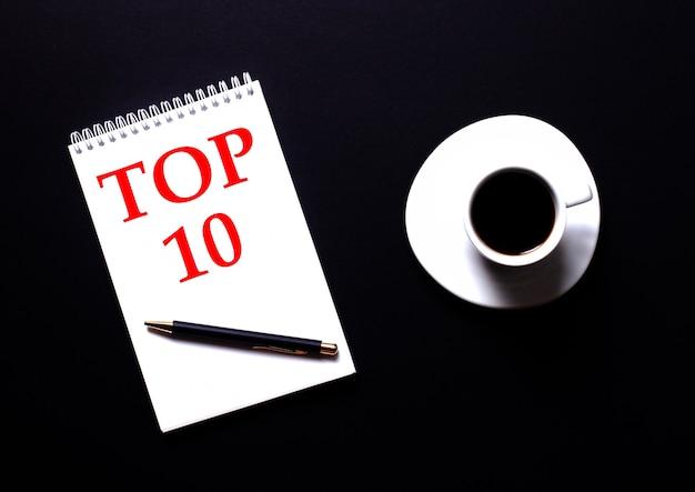 黒いテーブルの上の白い一杯のコーヒーの近くに赤いタイプの白いノートに書かれたtop10