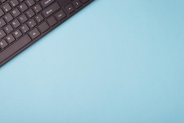 위의 상단은 빈 공간이 있는 파란색 배경에 있는 검은색 키보드의 평평한 평면 평면 오버헤드 보기 사진을 닫습니다.