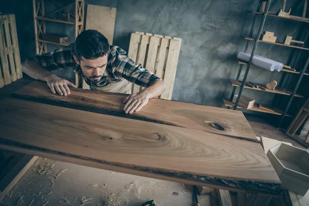 Вверху над высоким углом сконцентрированный прораб проверяет, насколько гладко его готовый отремонтированный плиточный стол носит клетчатую рубашку в доме, на рабочем месте в гараже