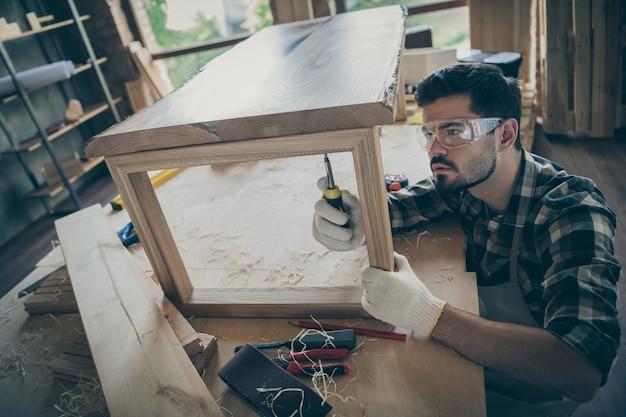 Вверху над высоким углом сфокусированный рабочий обновляет плиточную мебель, деревянный стол, использует отвертку в доме, домашнем гараже, на рабочем месте