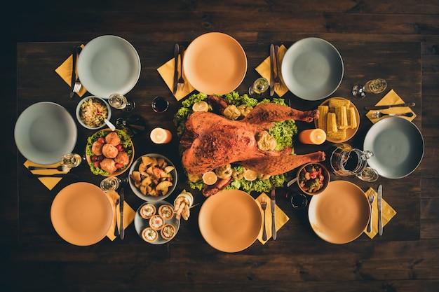 Вверху вверху фотография под большим углом запеченного жаркого, фаршированного индейкой, напитки, гарниры, овощной декор, пустые тарелки, ужин, две зажженные свечи в гостиной, без людей в помещении