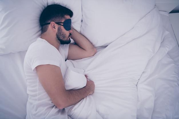 Вверху вверху под высоким углом в профиль, вид сбоку, его портрет красивый ухоженный привлекательный бородатый парень, лежащий на белой кровати, отдыхает, спит, в маске для глаз жизнеспособность ночью поздно вечером в домашней комнате