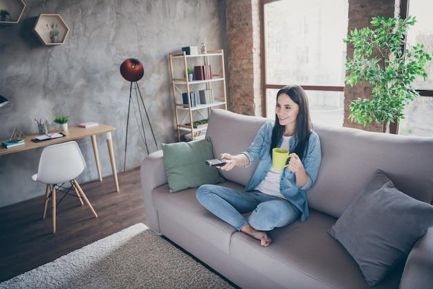 ポジティブな陽気な女の子のハイアングルビューのフルサイズの写真の上にcovid19の自由時間の検疫があります時計のテレビスイッチチャンネルがコーヒー飲料のマグカップを保持します