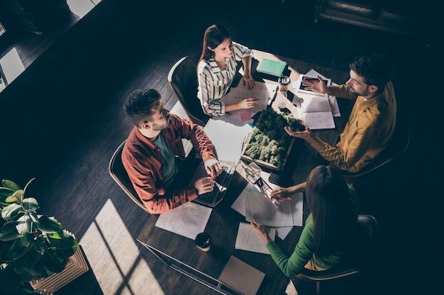 회사 재무 보고서를 논의하는 캐주얼 정장 차림의 바쁜 경험이 풍부한 기업인 4 명의 높은 각도보기 위의 상단