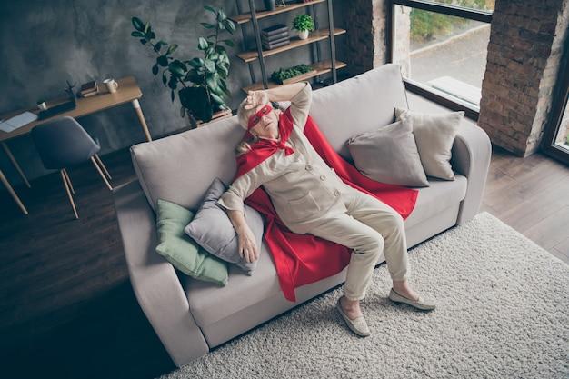 Вверху над высоким углом, вид на нее, она красивая, привлекательная, уставшая, больная, больная, седая бабушка в красном костюме, лежа на диване в промышленном кирпичном лофте, интерьер дома в современном стиле.