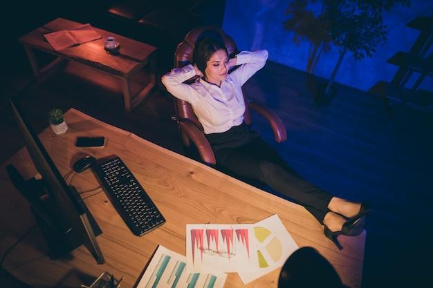 Вверху над высоким углом вид на красивую привлекательную стильную шикарную мирную спокойную женщину, топ-менеджер, адвокат, адвокат, владелец агентства финансовой компании, отдыхающий ногами на рабочем столе в темное время суток, рабочее место станции