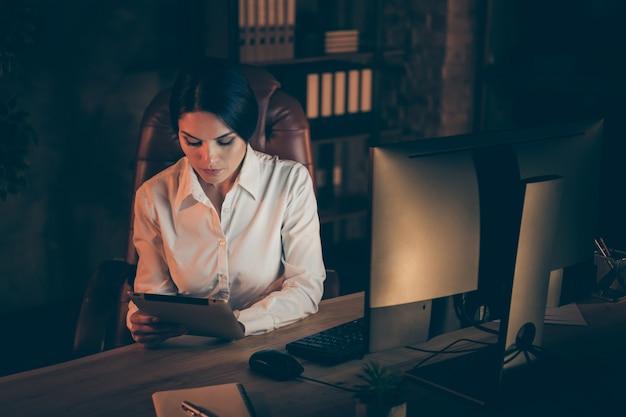 Вверху сверху вид под большим углом симпатичной привлекательной стильной умной умной опытной женщины-финансиста-экономиста, использующей цифровую электронную книгу, анализирующий отчет, план, доход, прибыль, инвестиционная ставка, ночь, темное рабочее место, станция