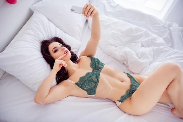 彼女のハイアングルビューの肖像画の上に彼女は素敵なフィットスリムスポーティなほっそりした完璧な形の魅力的な愛らしい女の子がベッドに横たわって自分撮りを撮って写真を送る夫ライトホワイトインテリアハウスアパート
