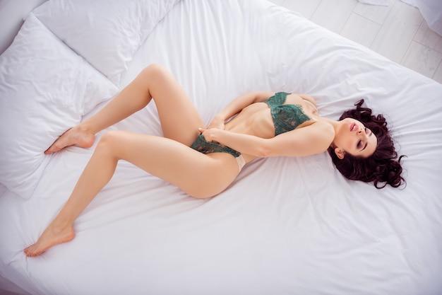 그녀의 높은 각도 보기 초상화 위에 그녀는 슬림 스포티 날씬한 날씬한 낚시를 좋아하는 매력적인 사랑스럽고 세련된 멋진 소녀가 기쁨 여가 고립을 즐기는 자신을 만지고 침대에 누워