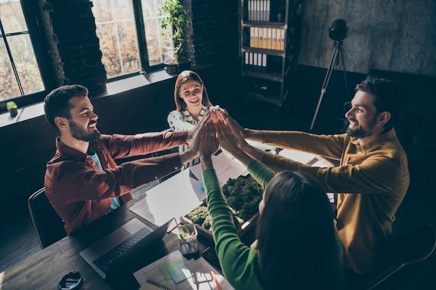높은 각도보기 전문 캐주얼 스타일의 사람들이 책상 테이블에 앉아 하이 파이브 스택 손을 올려 기업 창업 목표 달성