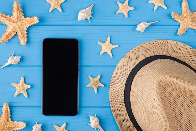 Вверху над головой крупным планом фото цифрового телефонного устройства с пустой шляпой от солнца в виде морской ракушки с сенсорным экраном на ярком цветном фоне