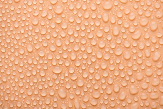 오버 헤드 위의 상단은 복숭아 배경에 물방울의 사진 사진을 닫습니다.