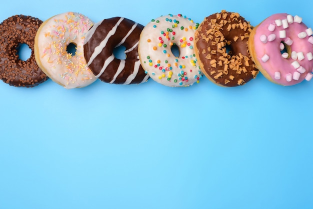 블루 팝 파스텔 배경 위에 절연 행에 누워 맛있는 스타일 많은 도넛의 오버 헤드 근접 촬영 평면 누워 flatlay보기 사진 위의 상단