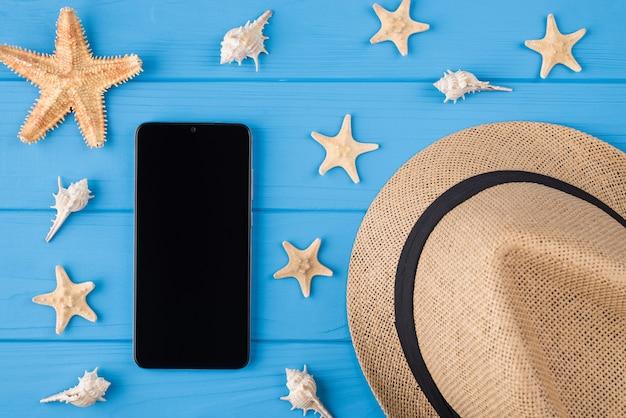 Вверху сверху крупным планом вид на фото черного цифрового гаджет-телефона с множеством ракушек и соломенной кепкой, изолированных на деревянном фоне