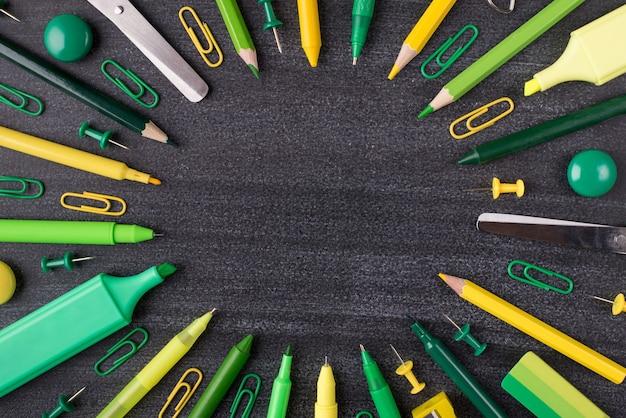 コピースペースで黒板に分離された緑と黄色の文房具の俯瞰図のクローズアップ写真の上の上