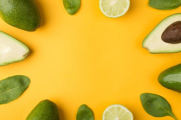 黄色の背景に分離されたカットアボカド、レモン、ほうれん草の葉の俯瞰図のトリミングされた写真の上の上部