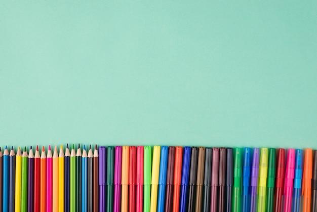 Вверху сверху вид плоской фотографии ряда разноцветных карандашей и маркеров, изолированных на бирюзовом фоне с copyspace
