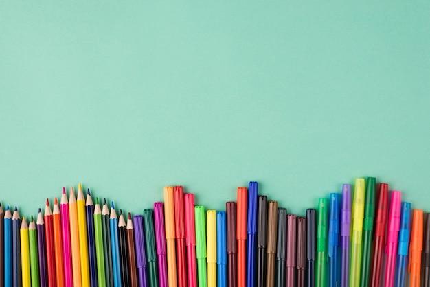 오버헤드 뷰 플랫레이 위에 있는 여러 색상의 크레용 펜 및 마커가 카피스페이스가 있는 청록색 배경에 격리된 사진