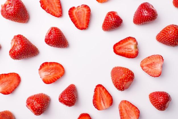 俯瞰写真の上の上部全体と白い背景で分離された円を作るイチゴをカット