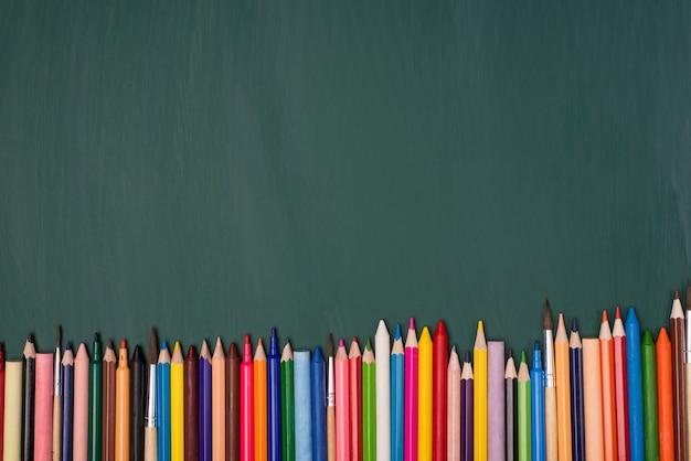 グリーンボード上で分離されたカラフルな鉛筆の俯瞰写真の上の上