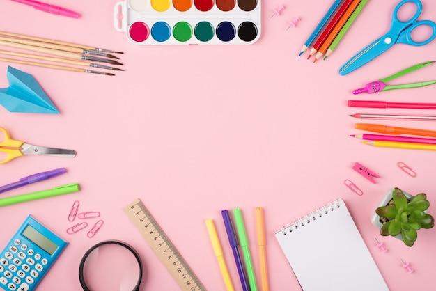 Фотография красочных канцелярских принадлежностей и суккулентов, изолированных на пастельно-розовом фоне с copyspace в центре, сверху сверху.