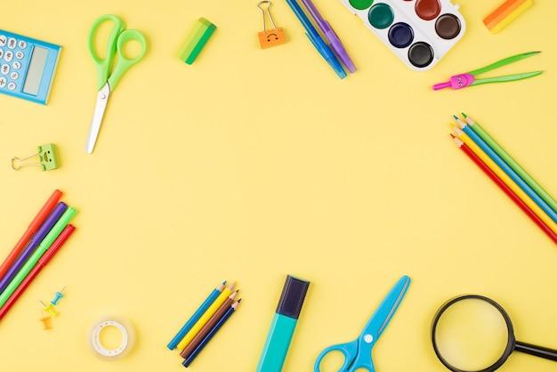 중앙에 카피스페이스가 있는 노란색 배경에 격리된 다채로운 편지지의 오버헤드 뷰 사진 위