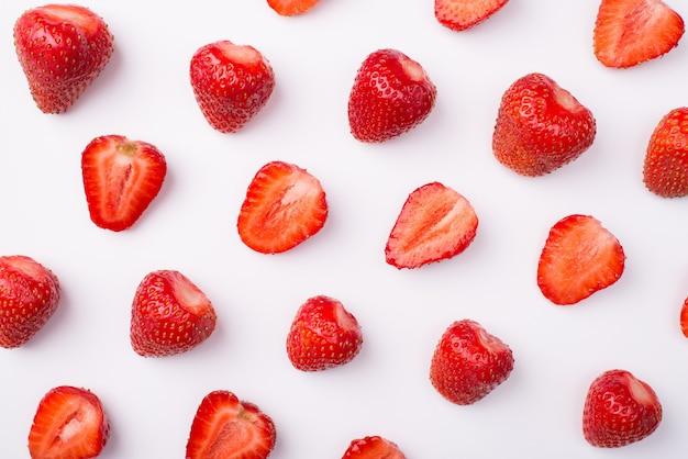 カットされたイチゴの列の俯瞰写真の上の上部は、白い背景で隔離された全体のものと交互になります
