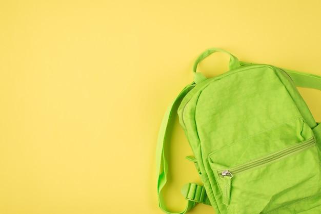Фотография зеленого рюкзака на желтом фоне с пустым пространством copyspace сверху сверху.