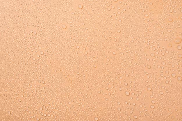 Фотография маленьких капель воды на бежевой поверхности сверху сверху сверху