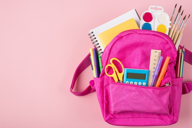 Фотография розового рюкзака и красочных канцелярских принадлежностей, размещенных справа вверху над сверху, изолирована на пастельно-розовом фоне с copyspace
