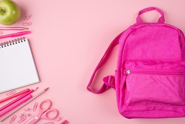 Фотография розового рюкзака, зеленого яблока и красочных канцелярских принадлежностей, изолированных на пастельно-розовом фоне.