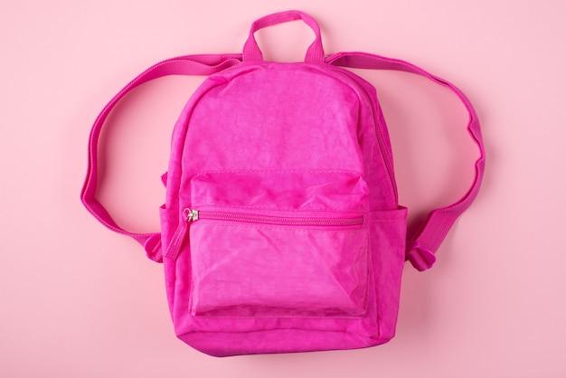 Вид сверху фото розового рюкзака, изолированного на пастельно-розовом фоне