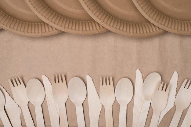 クラフト紙の背景テーブルに分離された木製のカトラリーと紙皿の列の俯瞰写真の上の上