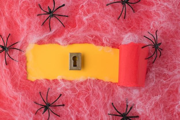 Вверху над головой вид на разорванную красную бумагу и замочную скважину на желтом фоне с пауками и паутиной