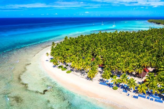 청록색 바닷물, 보트, 야자수가 있는 아름다운 해변의 최고 공중 무인 항공기 보기. saona 섬, 도미니카 공화국. 파라다이스 열 대 섬 자연 배경입니다.